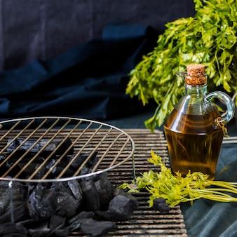 Folha de metal circular em carvão com garrafa de óleo e coentro sobre a mesa