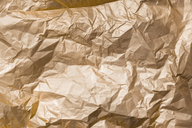 Folha de metal de folha de metal vincada brilhante de textura abstrata de ouro.