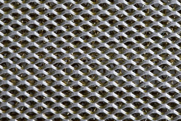 Folha de metal de fundo coberta com linhas de orifícios circulares
