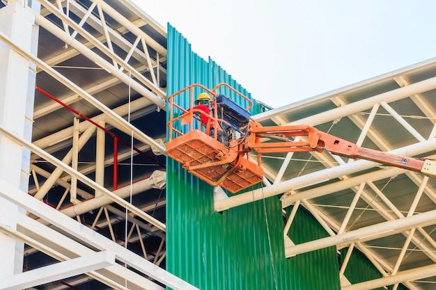 Folha de metal de instalação de trabalhadores de construção no novo edifício