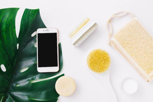 Folha de monstera com smartphone; bucha; hidratante; escova de pedra sabão e pedra-pomes sobre fundo branco