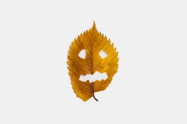 Folha de outono amarela com cara de halloween, isolada no fundo branco.