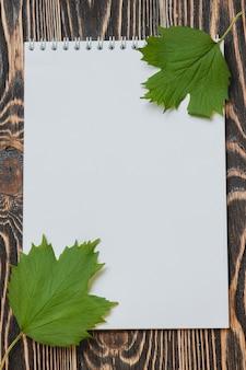 Folha de outono com uma folha em branco na mesa de madeira