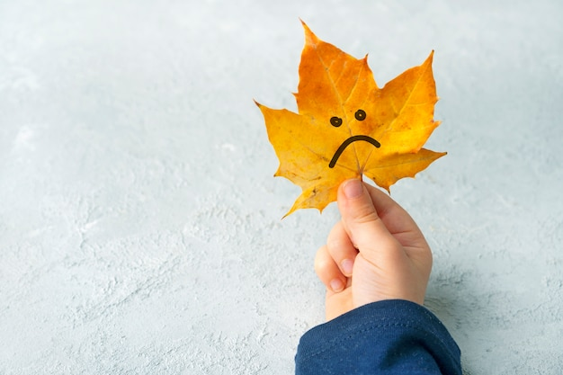 Folha de outono triste nas mãos de uma criança. conceito de outono.