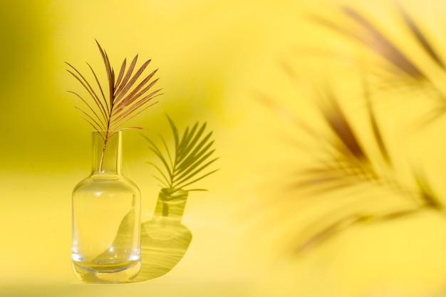 Folha de palmeira dourada em vaso de vidro.