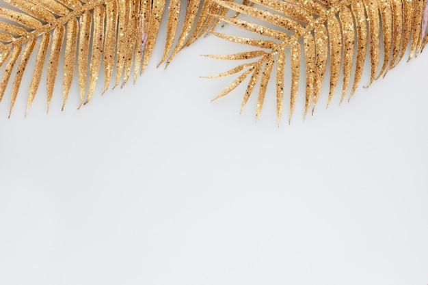 Folha de palmeira dourada sobre fundo azul