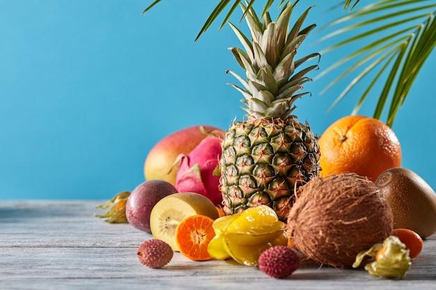 Folha de palmeira exótica de várias frutas em uma mesa de madeira cinza