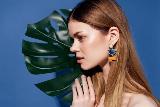 Folha de palmeira verde linda mulher posando com fundo azul