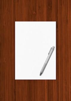 Folha de papel a4 em branco e modelo de maquete de caneta isolado em fundo escuro de madeira