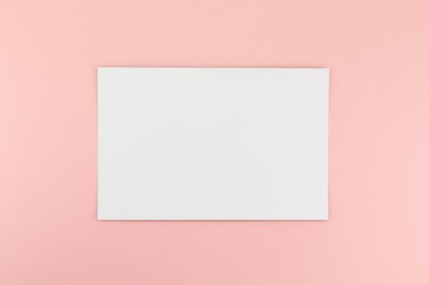 Folha de papel a4 em branco sobre fundo rosa
