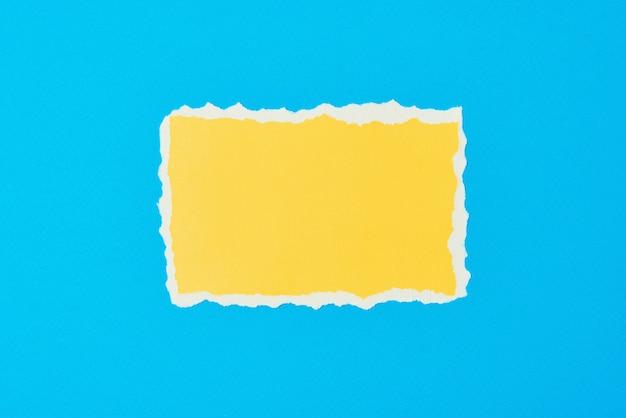 Folha de papel amarelo rasgado com borda rasgada em azul