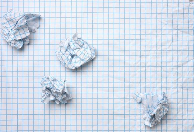 Folha de papel amassada em branco em uma gaiola e bolas amassadas, vista de cima