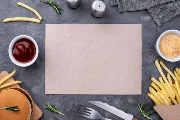 Folha de papel ao lado de hambúrguer e batatas fritas