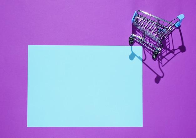 Folha de papel azul para o espaço da cópia, mini carrinho de compras na mesa roxa. mesa de compras criativa