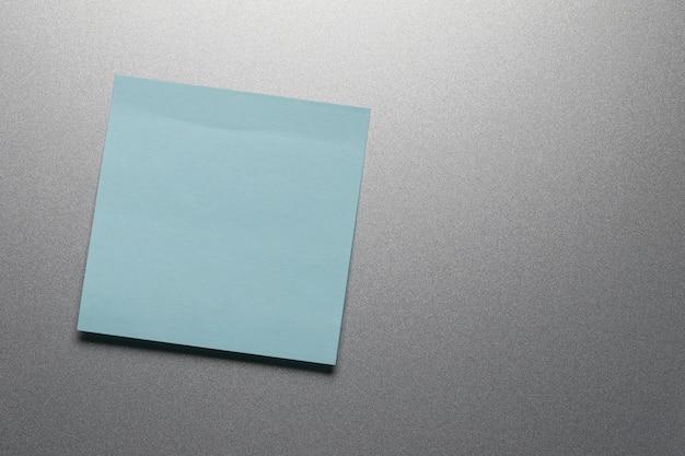 Folha de papel azul vazia na porta da geladeira.