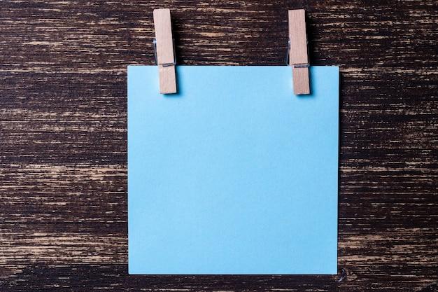 Folha de papel azul vazia para anotações com prendedores de roupa em fundo de madeira. cartões em branco no modelo de maquete. prendedores de roupa de madeira com folhas de papel. conceito de negócio, copie o espaço