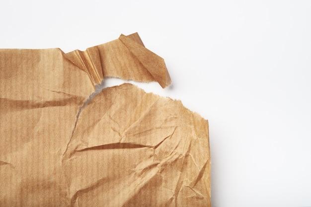Folha de papel bege amassada e rasgada isolada no fundo branco