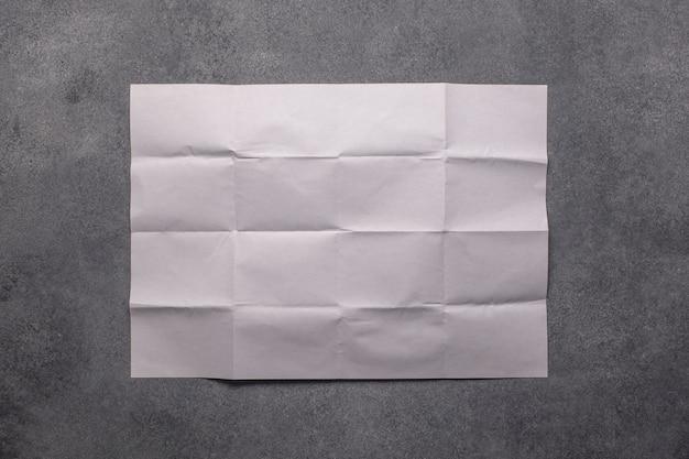 Folha de papel branca com dobras na parede de concreto