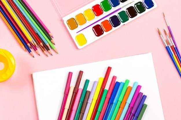 Folha de papel branca em branco com lápis de cor e tintas