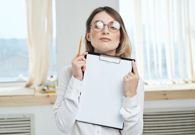 Folha de papel branca mulher hospedando-se perto do interior da janela pasta com documentos. foto de alta qualidade