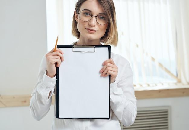Folha de papel branca mulher hospedando-se perto do interior da janela pasta com documentos