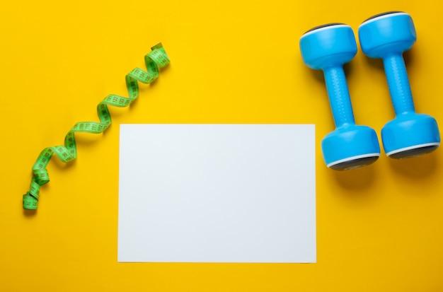 Folha de papel branca para espaço de cópia, halteres de plástico, régua na tabela amarela. mesa de fitness criativa