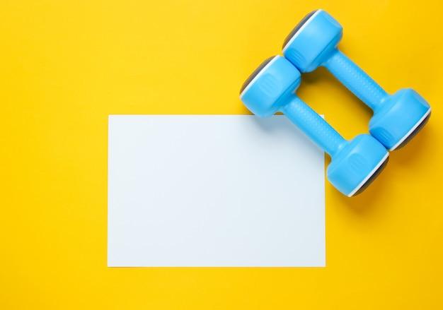 Folha de papel branca para o espaço da cópia, halteres plásticos na tabela amarela. mesa de fitness criativa