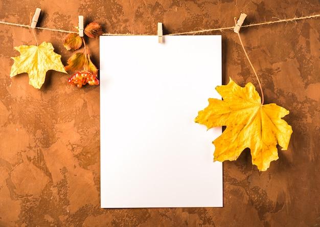 Folha de papel branca vazia e folhas secas penduram em prendedores de roupa em marrom