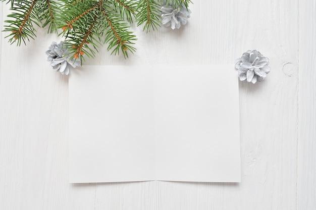 Folha de papel branca vazia em um fundo do white christmas de ramos e de cones do abeto. carta para o papai noel