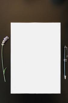 Folha de papel branca vertical ao lado de uma alfazema e uma caneta sobre uma mesa escura