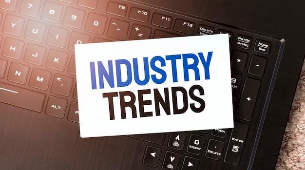 Folha de papel branco com o texto tendências da indústria no laptop preto