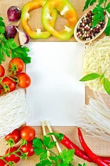 Folha de papel branco, moldura feita de macarrão de arroz, tomate, pimentão, salsa, manjericão e alho em uma sacola