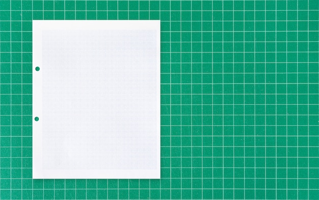 Folha de papel branco no tapete verde.