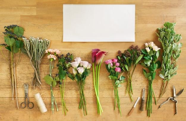 Folha de papel branco vazia e buquês de flores frescas e amoras na mesa de madeira, vista superior. rosas e callas de coral