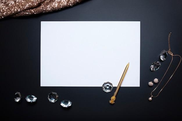 Folha de papel branco vazia joias e outros acessórios no fundo preto espaço livre