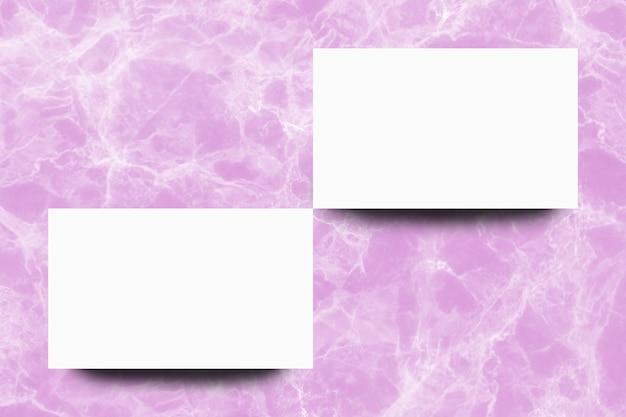 Folha de papel branco vazio no fundo de mármore rosa