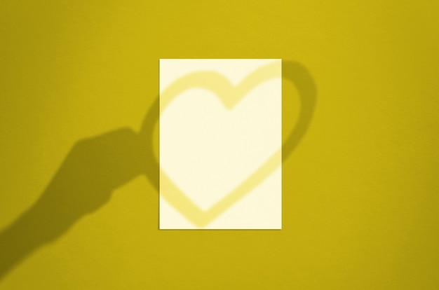 Folha de papel branco vertical em branco de 5 x 7 polegadas com sobreposição de sombra de mão e coração. cartão de dia dos namorados moderno e elegante ou simulação de convite de casamento.