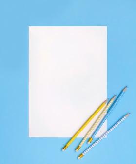 Folha de papel com lápis listrado azul e amarelo.