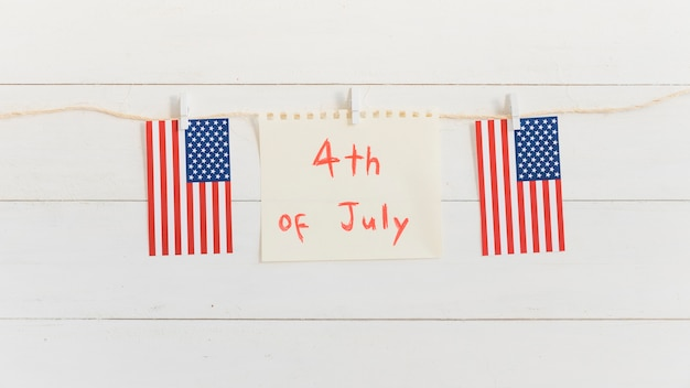 Folha de papel com texto em 4 de julho e pequena bandeira americana