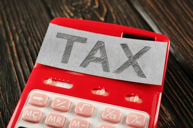 Folha de papel com texto tax na calculadora vermelha