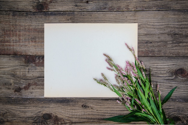 Folha de papel e as pequenas flores cor de rosa em fundo de madeira