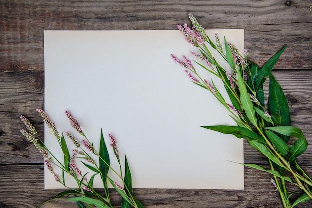 Folha de papel e as pequenas flores cor de rosa na mesa de madeira