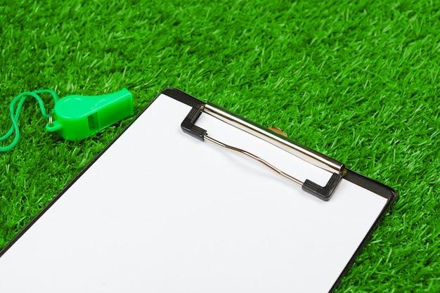 Folha de papel e equipamentos esportivos em close-up de grama