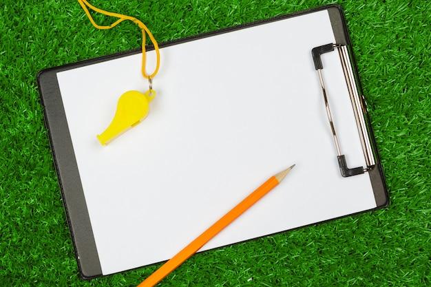 Folha de papel e equipamentos esportivos na grama