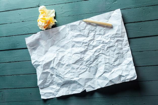 Folha de papel e lápis amassado