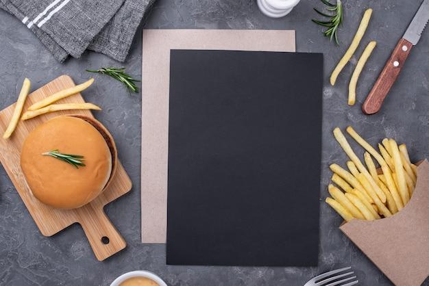 Folha de papel em branco ao lado de hambúrguer e batatas fritas