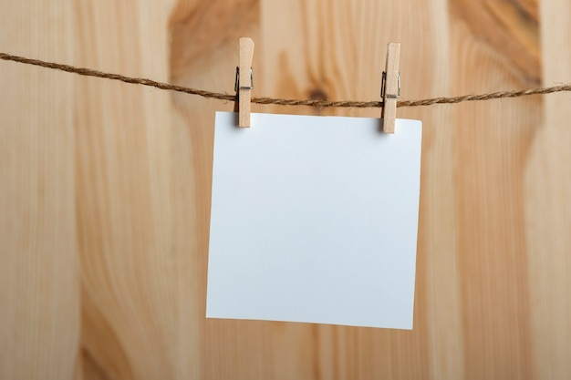 Folha de papel em branco branca com prendedores de roupa na corda em fundo de madeira. copie o espaço, maquete.