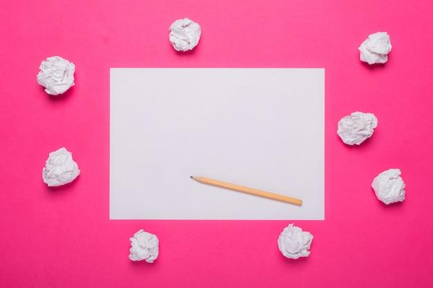 Folha de papel em branco branco, lápis de madeira e bolas de papel amassado na rosa