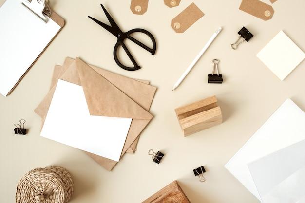 Folha de papel em branco com envelope na mesa bege. camada plana, vista superior