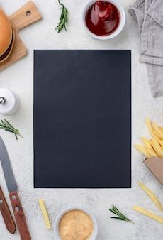 Folha de papel em branco com hambúrguer e batatas fritas